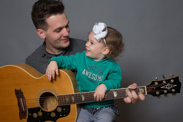 Guy with his daughter and guitar